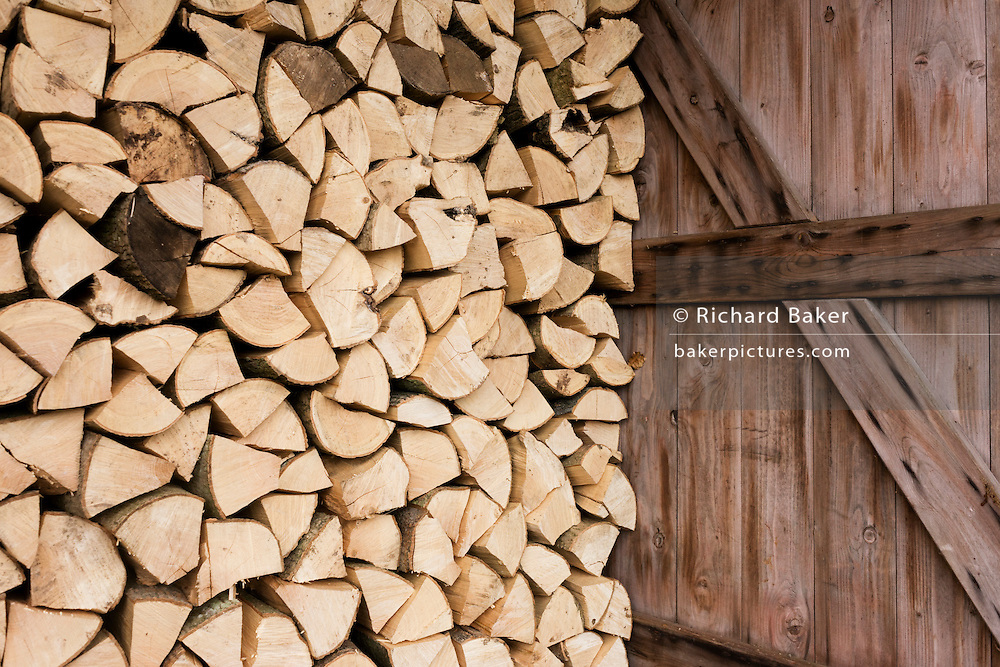 Piles of sawn logs and open door, ready for a winter home fire, stays dry under cover on a small holding.
