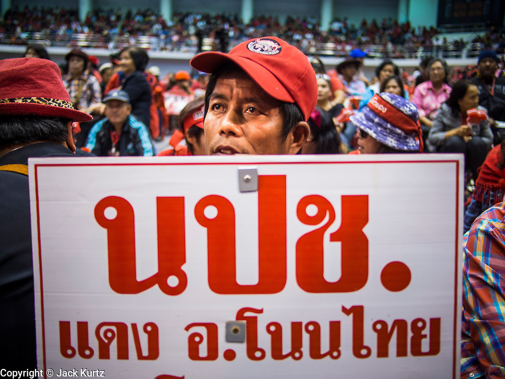 "23 FEBRUARY 2014 - NAKHON RATCHASIMA (KORAT), NAKHON RATCHASIMA, THAILAND: A Red Shirt supporter at the Red Shirt meeting in Korat. The United front of Democracy against Dictator (UDD or Red Shirts), which supports the elected government of Yingluck Shinawatra, staged the ""UDD's Sounding of the Battle Drums"" rally in Nakhon Ratchasima (Korat) to counter the anti-government protests that have gripped Bangkok since November. Around 4,000 of UDD's regional and provincial coordinators along with the organization's core members met at Liptapunlop Hall inside His Majesty the King's 80th Birthday Anniversary Sports Complex in Korat to discuss the organization's objectives and tactics against anti-government protestors, which the UDD says ""seek to destroy the country's democracy."" The UDD leadersa announced that they will march to Bangkok and demonstrate against anti-government protests led by Suthep Thaugsuban.   PHOTO BY JACK KURTZ"