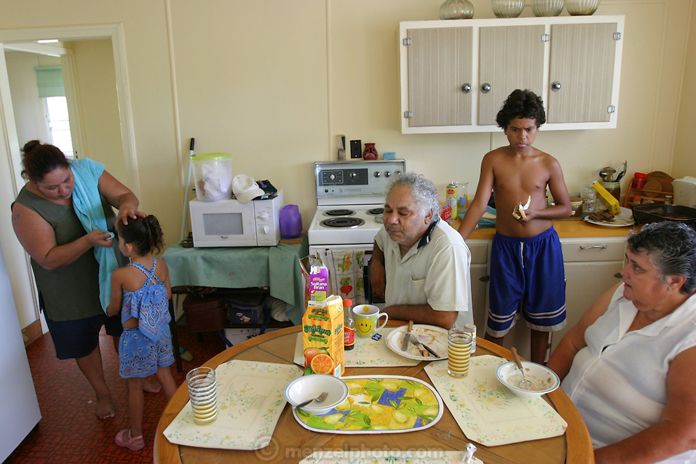 (MODEL RELEASED IMAGE). Breakfast during the children's summer vacation at the Brown family home in Riverview, Australia (outside of Brisbane) is low-key and unstructured. Everyone eats when the mood strikes them. This morning Doug cooked himself a hearty breakfast of fried meat, onions, gravy, and buttered toast, while overseeing his wife's meal of cereal and juice. Since her stroke, Marge has been trying to eat a more healthy diet. Also pictured are Vanessa attending to daughter Sinead, and Rhy standing at the counter eating a sandwich. (Supporting image from the project Hungry Planet: What the World Eats.)