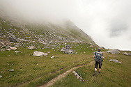 Hiking in low cloud on Maja e Qenit, on the Kosovo side of the border ridge, Peaks of the Balkans trail © Rudolf Abraham