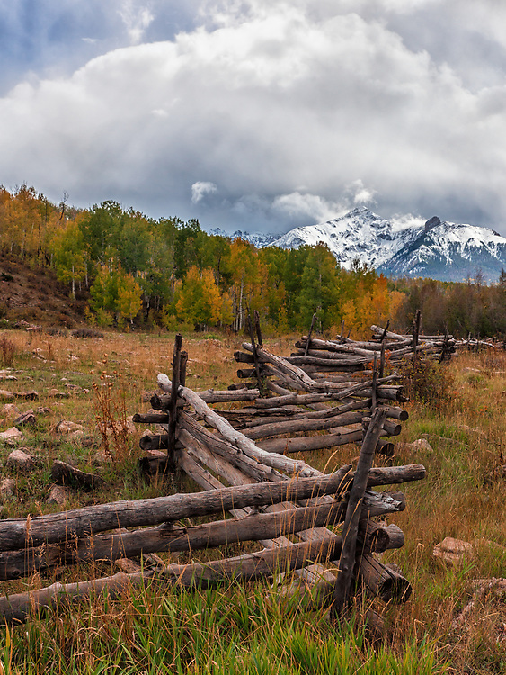 A shot of a fence line with a dramatic backdrop of Mountains.