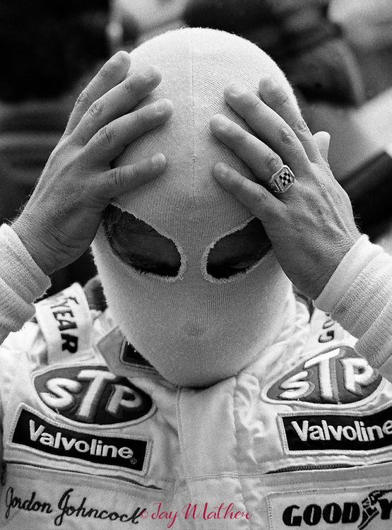 """Gordon Johncock adjusts his fire retardant head cover before putting on his racing helmet at the start of the 1982 Indianapolis 500 race.  He wears the ring he won for his 1973 victory.  """"Gordy"""" would win his second 500 over Rick Mears by a margin of 0.16 seconds, the closest finish up to that point in Indy 500 history.  May 30, 1982."""