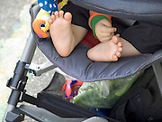 little baby feet and hand sticking out of a stroller