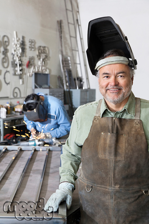 Portrait of a happy mature man wearing welding mask with young male working in background