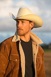 cowboy in a sheepskin jacket at sunset