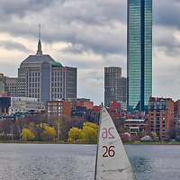 Boston skyline photography featuring iconic landmarks along the Charles River, such as the Prudential Center and 200 Clarendon better known as the John Hancock Building. Partly cloudy skies were in the weather forecast and a bit hesitant to explore, but boy am I glad I went. The sailing boat added a colorful punch while the overcast sky showed beautiful grey tones and different cloud formations. <br />