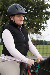 Woman with visual impairment having riding lesson.