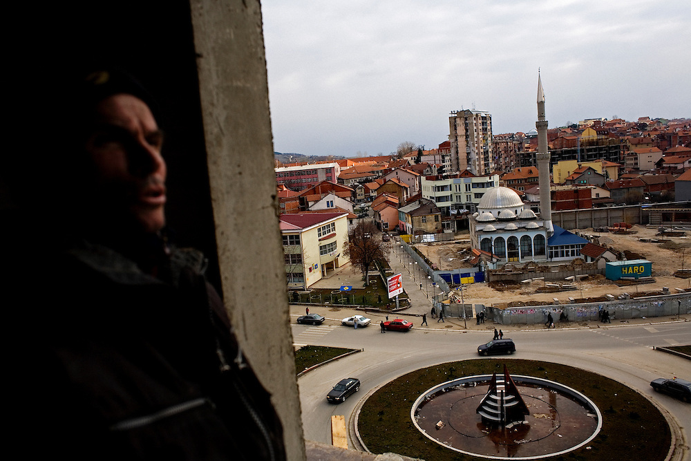 Constructions workers at a new apartment building that is rapidly going up in Mitrovica, Kosovo. The central mosque is seen in the background. The Albanian side of Mitrovica is experiencing a boom in construction with more than a dozen new, large apartment and commercial spaces being constructed currently...Mitrovica, February 15, 2009.