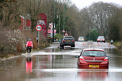 © Licensed to London News Pictures. 24/12/2013<br /> A cyclist  pedals through the flood water . <br /> London Road A224  Polhill in Halstead, Kent is closed with cars abandoned in 4 feet of rain water overnight.<br /> The UK  has woken up to trees and electricity cables down following a night of gale-force winds and torrential rain.<br /> Photo credit :Grant Falvey/LNP