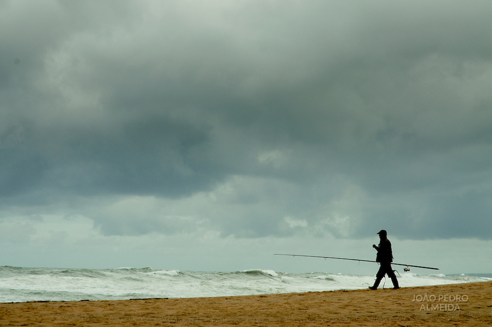 Man walking by the beach in cloudy day
