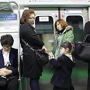 South Korean's traveling on the Seoul Metropolitan Subway, Seoul, South Korea. 22nd March 2012. Photo Tim Clayton