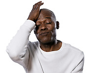 Close-up of a displeased afro American man with hand on head puffing in studio on white isolated background