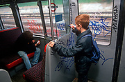 Seen from behind, two young boys tag the inside the 1980s carriage of a 1990s London Underground train, on 8th November 1989, in London, England. in 1980s London, graffiti was a persistent problem that costs the transport company network up to £3 million a year to remove. If caught, juvenile delinquents like usually escaped with only a caution because of their age - although older ones were prosecuted. (Photo by Richard Baker / In Pictures via Getty Images)
