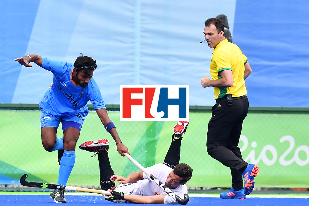 India's Surender Kumar (L) vies with Canada's Matthew Sarmento during the mens's field hockey India vs Canada match of the Rio 2016 Olympics Games at the Olympic Hockey Centre in Rio de Janeiro on August, 12 2016. / AFP / MANAN VATSYAYANA        (Photo credit should read MANAN VATSYAYANA/AFP/Getty Images)