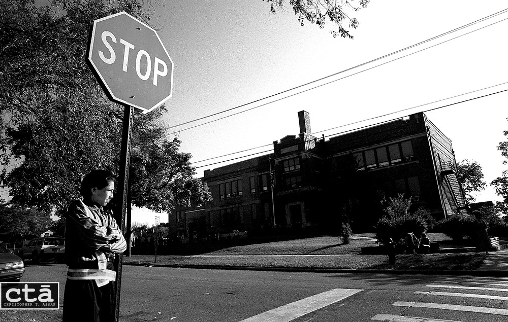 Before the final day of classes at Grant Elementary School, Daniel Barajas, a sixth-grade student, waits to help students cross the street as part of his safety patrol responsibilities. The 112-year-old school is closing after the district decided it would be too expensive to overhaul.<br /> <br /> <br /> As everyone scurried to pack up their pens, papers and paintshirts, a thirdgrade student paused momentarily to listen to the faint sound of chimes.<br /> <br /> <br /> &quot;I can hear the bell,&quot; she announced, a hint of sorrow in her voice.<br /> <br /> <br /> Silence immediately fell over the classroom as everyone stopped and turned toward the window. For a few seconds they all listened as the school bell continued to ring at somewhat even intervals.<br /> <br /> <br /> After 112 years, Grant Elementary School in Elgin wrapped up its final school year. The two story, red-brick building was tagged for closure five years ago by a team of building experts. Its cavernous basement and a difficult floor plan were deemed beyond repair or renovation. Students will be sent to neighboring schools instead.<br /> <br /> <br /> &quot;It's old, but it's not like really trashy,&quot; fifth-grader Diana Tinajero said.<br /> <br /> &quot;I've touched a lot of lives in here,&quot; said Shirlene Hogue, who began her teaching career at Grant 23 years ago. &quot;I hope it's been a positive experience for them.&quot; -by Charla Brautigam.