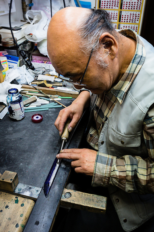 While working on a shinken (a true sword, with a real cutting edge), a worker applies a blue compound to the blade to prevent it from rusting.