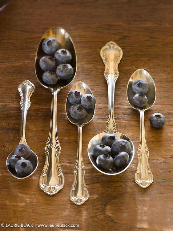 Blueberries in vintage silver spoons