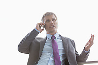 Low angle view of businessman talking on cell phone against sky