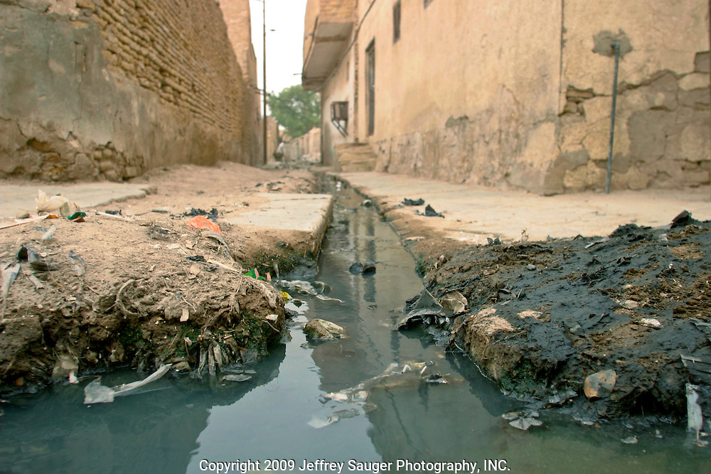 Crude gutters flow with raw sewage as children play in the modernized center of the village Suq ash Shuyukh, about 20 miles southeast of Nasiriyah, Iraq, Wednesday, July 30, 2003.  ..Since the 1991 uprising against Saddam Hussein in Shiite dominated Southern Iraq, people of this area have suffered greatly through his methods of disrupting daily life. For example, modernization came to a hault as money was diverted to Baath Party strongholds. Check points on on every other corner made it nearly impossible to go to work, the doctor, or visit family. Teachers made $5 U.S. per month and had to spend almost all of their salary for taxis in order to go to work...He tried to kill the people by cutting off the rivers that village survival depends on. Dams and canals dirverted the fresh water from flowing into the swamps by way of tributaries. In effect, without fresh water flowing in, the people started poisoning the water supply themselves by using it to wash and clean. Their primitive sewers still flow freely into the same waters that animals use and that feed their rice fields.
