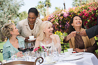 Female friends drinking at outdoor table