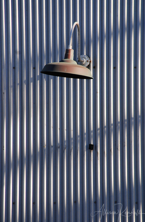 Late afternoon light casts shadows across corrugated metal siding, a graceful lamp adds interest in an industrial area of Monterey