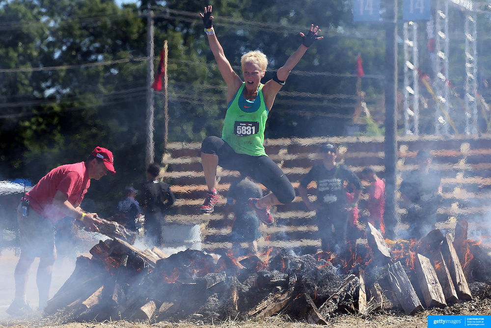 Traci Artioli in action at the fire jump obstacle during the Reebok Spartan Race. Mohegan Sun, Uncasville, Connecticut, USA. 28th June 2014. Photo Tim Clayton