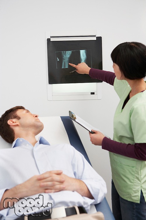 Doctor examining x-ray with male patient in hospital