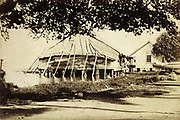 Indigenous house on stilts with thatched roof, on Bora Bora in the Society Islands, photograph, 1885-94, by G Spitz, in the MTI-TFM Collection (fonds de la Polynesie Francaise), in the Musee de Tahiti et des Iles, or Te Fare Manaha, at Punaauia, on the island of Tahiti, in the Windward Islands, Society Islands, French Polynesia. The Museum of Tahiti and the Islands was opened in 1974 and displays collections of nature and anthropology, habitations and artefacts, social and religious life and the history of French Polynesia. Picture by Manuel Cohen
