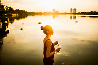 A woman drinks a ginger-lemongrass martini on the banks of the Saigon River at The Deck bar and restaurant in Ho Chi Minh City, Vietnam.