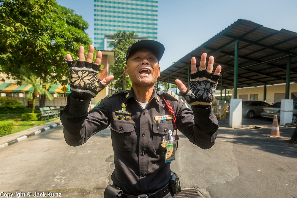 """01 FEBRUARY 2014 - BANGKOK, THAILAND: A Thai police officer tries to stop voters who stormed the Din Daeng polling place after it was declared closed because anti-government protestors blocked access to the polls. Thais went to the polls in a """"snap election"""" Sunday called in December after Prime Minister Yingluck Shinawatra dissolved the parliament in the face of large anti-government protests in Bangkok. The anti-government opposition, led by the People's Democratic Reform Committee (PDRC), called for a boycott of the election and threatened to disrupt voting. Many polling places in Bangkok were closed by protestors who blocked access to the polls or distribution of ballots. The result of the election are likely to be contested in the Thai Constitutional Court and may be invalidated because there won't be quorum in the Thai parliament.    PHOTO BY JACK KURTZ"""