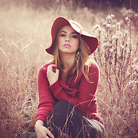 A beautiful  young woman with blonde hair wearing a red hat sitting in the gras