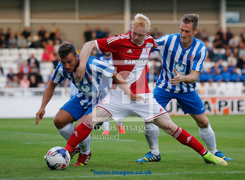 Luke Williams (center) of Middlesbrough holds off Michael Duckworth (left) and Neil Austin (right) of Hartlepool United during the pre season friendly match at Victoria Park, Hartlepool<br /> Picture by Simon Moore/Focus Images Ltd 07807 671782<br /> 30/07/2014
