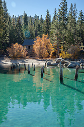 """Skunk Harbor, Lake Tahoe 1"" - Photograph of old pier pylons, yellow fall colored trees, and an old stone structure at Skunk Harbor, Lake Tahoe."