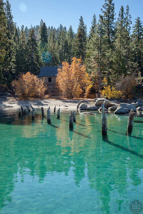 """""""Skunk Harbor, Lake Tahoe 1"""" - Photograph of old pier pylons, yellow fall colored trees, and an old stone structure at Skunk Harbor, Lake Tahoe."""