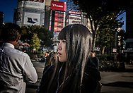 Detached, in thought, waiting for the light to change.  Shinjuku, Tokyo, Japan