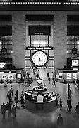 The iconic center of Grand Central Terminal as photographed from the down escalator from the PanAm Building. The view of the central concourse leads all the way to the 42nd Street doors. The backlighting comes from the 42nd Street doors and windows. About an hour before the noon rush. 1976.
