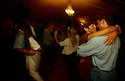 During a late-night party when the lights are low and the mood is intimate, couples smooch and cuddle under the roof of a garden marquee. The couple nearest embrace in a romantic close moment when the dance is slow and lovers can get close.