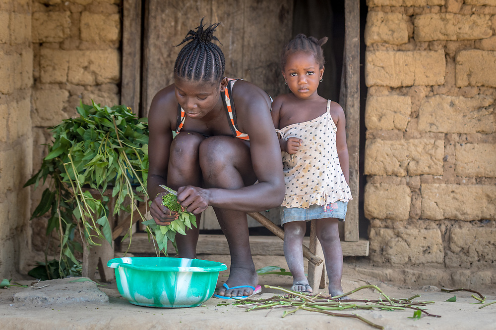 A girl cuts greens while a child stares at the camera in Ganta, Liberia