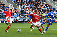 Zurab Khizanishvili of Reading (R) shoots past Stephen Foster (6) of Barnsley (centre) during the Npower Championship match between Reading and Barnsley on Saturday 25th September 2010 at the Madejski Stadium, Reading, UK. (Photo by Andrew Tobin/Focus Images)
