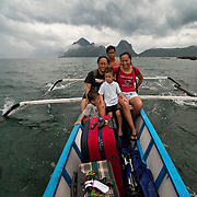 Family rides a water taxi to their resort, Pontoon boat in El Nido, Palawan, Philippines