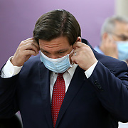 Florida Governor Ron DeSantis wears a face mask as he discusses how to safely reopen Florida salons with small business owners during a roundtable at OhSoooJazzy Hair Salon in Orlando, Florida on Saturday, May 2, 2020. (Alex Menendez via AP)
