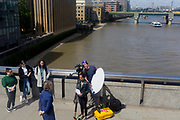 With the Southbank and Southwark Bridge in the background, a TV crew films a presenter overlooking the River Thames and the City of London, the capital's financial district, on 17th June 2019, in London, England.