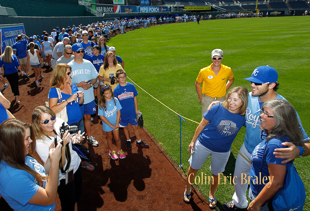 Kansas City Royals third baseman Mike Moustakas has his picture taken during Photo Day for season ticket holders before a baseball game against the Boston Red Sox at Kauffman Stadium in Kansas City, Mo., Sunday, Aug. 11, 2013. (AP Photo/Colin E. Braley)