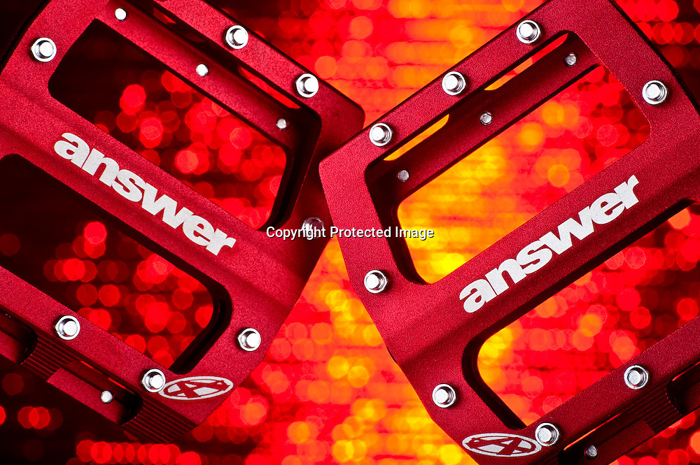 Red Answer flat pedals on a colorful studio background.