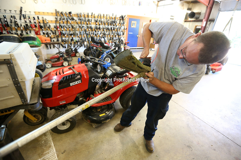 Terry Robbins, a service technician, replaces a speed feed head on a weedeater that a customer brought in. Robbins had the part in stock and made the repair as the customer waited.
