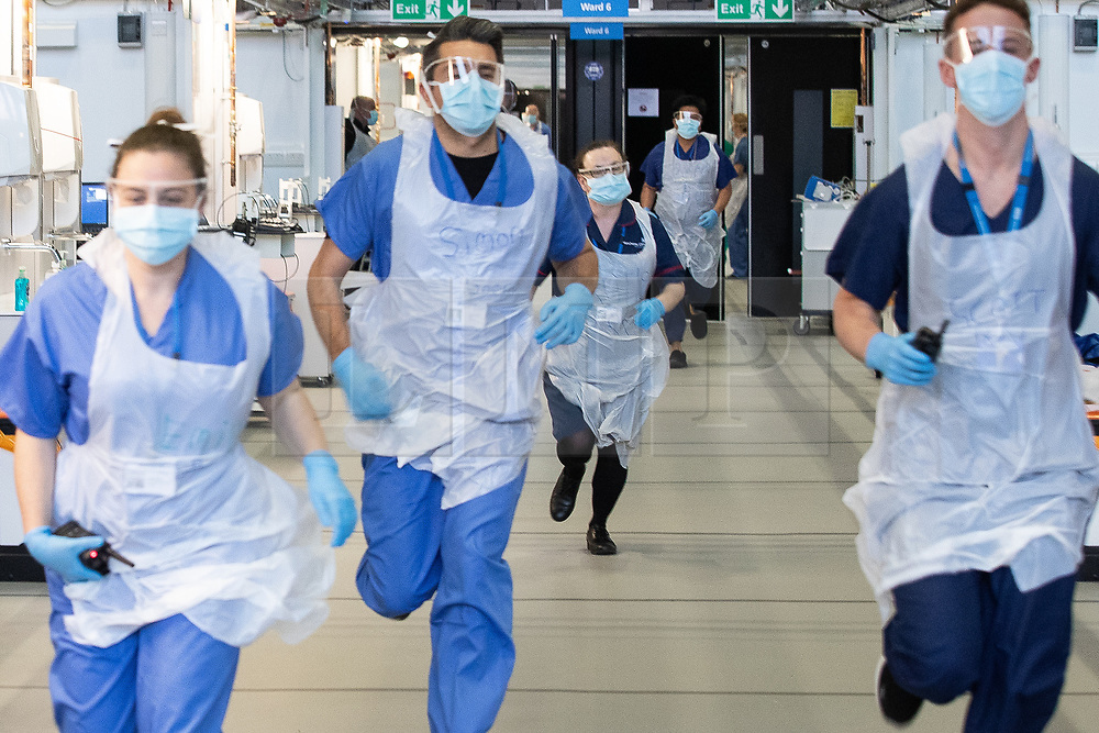 © Licensed to London News Pictures . 15/04/2020. Manchester, UK. Clinicians wearing PPE run through the hospital as they role play treating a patient in cardiac arrest (played by a ward nurse) in the dedicated resuscitation room of the Nightingale NW Hospital . The National Health Service has built a 648 bed field hospital for the treatment of Covid-19 patients , at the historical railway station terminus which now forms the main hall of the Manchester Central Convention Centre . The facility is due to fully open this week (ending Friday 17th April 2020 ) and will treat patients from across the North West of England , providing them with general medical care and oxygen therapy after discharge from Intensive Care Units . Photo credit : Joel Goodman/LNP