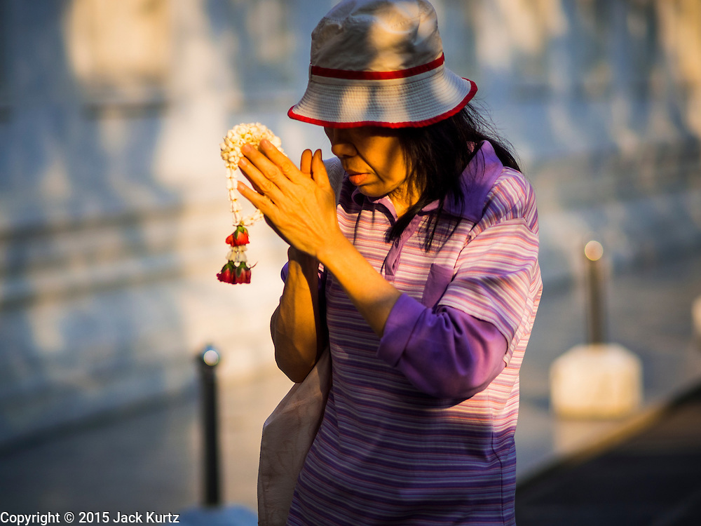 04 MARCH 2015 - BANGKOK, THAILAND:  A woman carries a flower garland while she prays and walks around the prayer hall at Wat Benchamabophit on Makha Bucha Day. Makha Bucha Day is an important Buddhist holy day and public holiday in Thailand, Cambodia, Laos, and Myanmar. Many people go to temples to perform merit-making activities on Makha Bucha Day. Wat Benchamabophit is one of the most popular Buddhist temples in Bangkok.   PHOTO BY JACK KURTZ