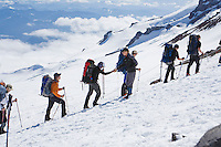 Rainier Mountaineering Guides meet their climbing clients as they arrive at camp Muir 10000 feet up Mt Rainier, Washington, Unitede States.