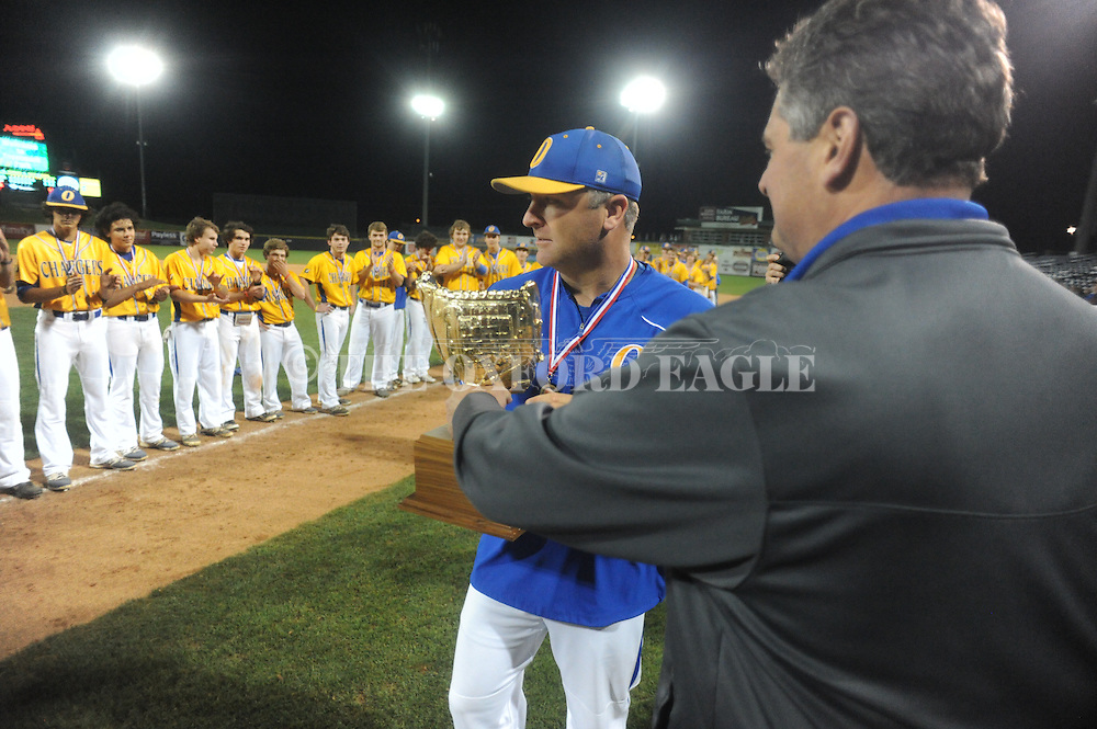 Oxford High coach Chris Baughman (left) accepts the championship trophy from superintendent Brian Harvey following the win vs. George County in the MHSAA Class 5A state championship at Trustmark Park in Pearl, Miss. on Thursday, May 21, 2015. Oxford won 9-0 to win its second state title in baseball and its first since 2005.