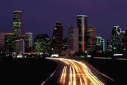 Night view of Houston, Texas skyline with motion blur of freeway traffic lights.
